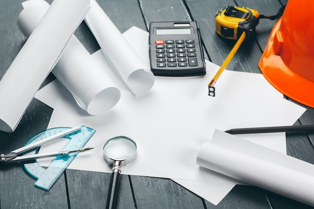 Posto di lavoro di ingegnere con schemi, bussola, matita e casco di sicurezza