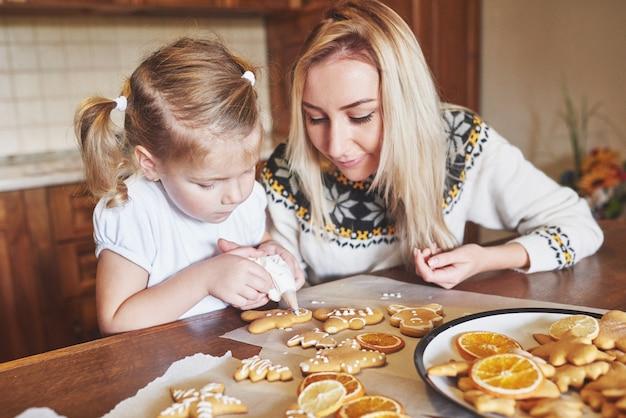 Posto di lavoro di pasticceria con le mani delle donne che decorano i biscotti di natale. panetteria a casa, dolce soleggiata, vacanze invernali.