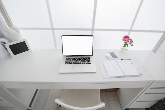 Posto di lavoro interno moderno con il computer portatile nei colori bianchi