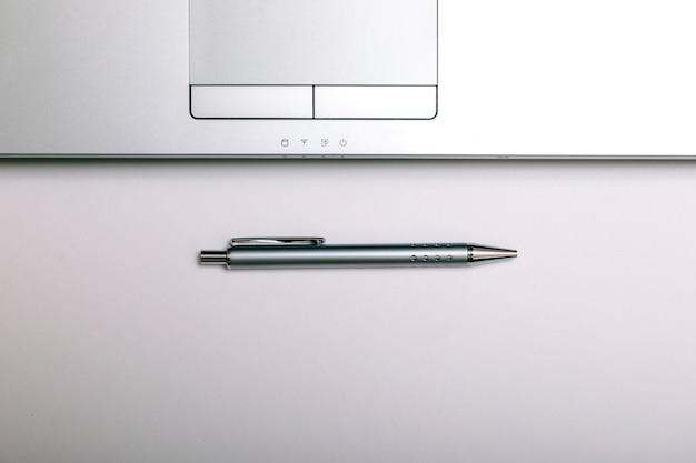 Posto di lavoro minimalista con la tastiera, la penna o la matita del computer portatile su fondo bianco