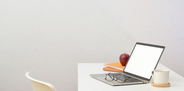 Posto di lavoro minimo con computer portatile aperto e articoli per ufficio sullo scrittorio bianco