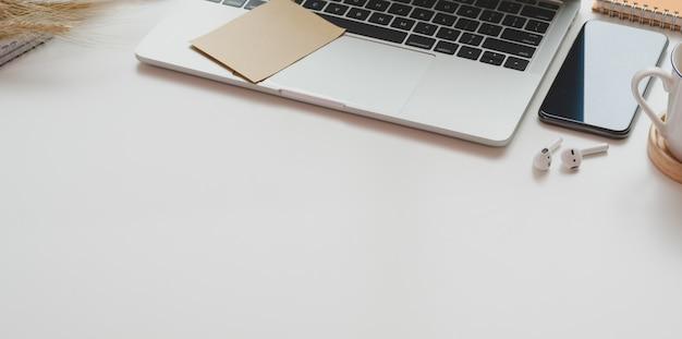 Posto di lavoro minimo con il computer portatile aperto con articoli per ufficio e lo spazio della copia