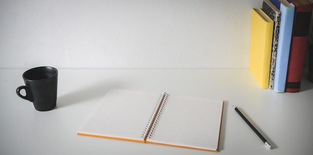Posto di lavoro minimo con il taccuino in bianco aperto, gli articoli per ufficio, la tazza di caffè e lo spazio della copia
