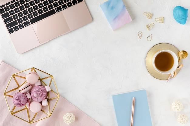 Posto di lavoro moderno bianco con il computer portatile e la tazza di tè.
