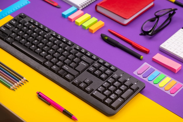 Posto di lavoro moderno con tastiera, diario, matite, penne e bicchieri su arancio-viola.