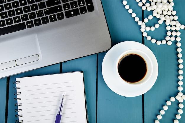 Posto di lavoro moderno delle donne con il taccuino o il computer portatile.