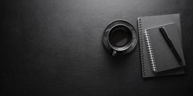 Posto di lavoro moderno scuro con la tazza e il taccuino di caffè sulla tavola di cuoio nera