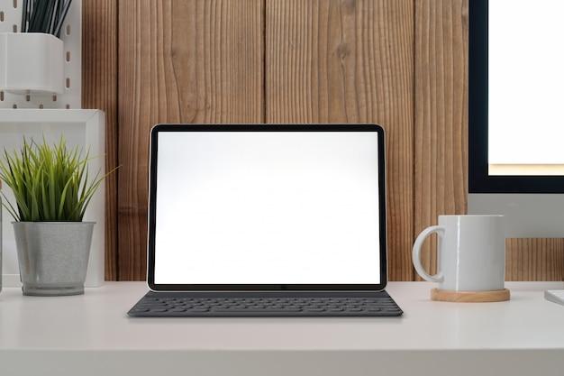 Posto di lavoro moderno ufficio con schermo vuoto tablet mockup, pc e forniture alla moda