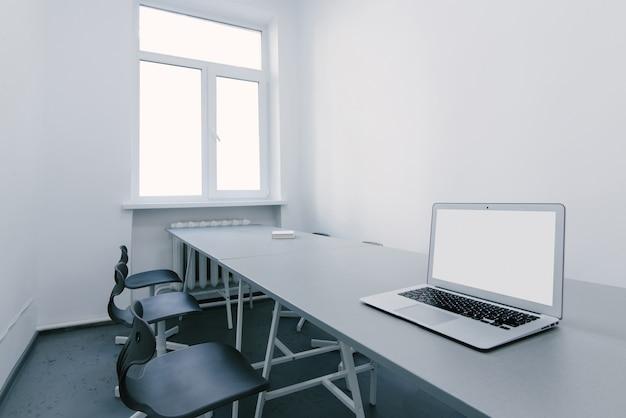 Posto di lavoro per un laptop in un ufficio leggero. spazio per i negoziati in ufficio. il portatile è sulla scrivania in ufficio.