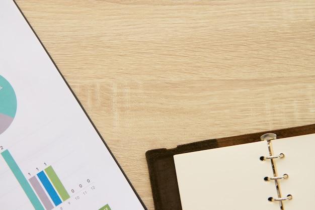 Posto di lavoro sul tavolo da ufficio con grafici e libro sul tavolo di legno. vista superiore con spazio di copia