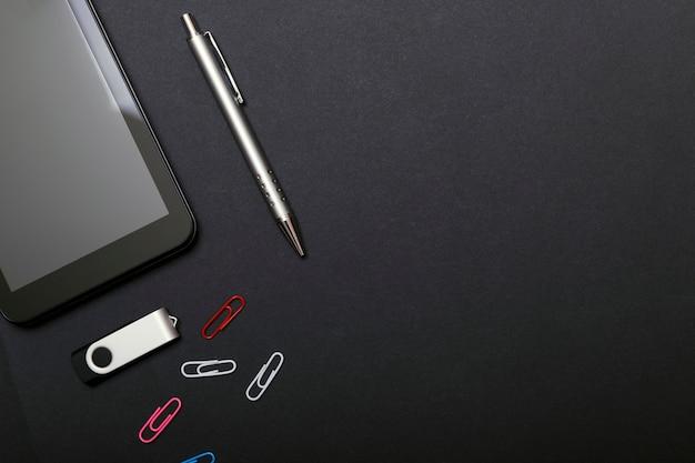 Posto di lavoro, tablet pc e smart phone sul tavolo nero.
