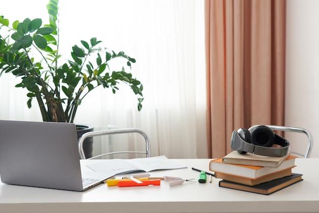 Posto di lavoro vuoto con il computer portatile e libri su uno scrittorio, interior design dello studente o impiegato indipendente, posto di lavoro domestico comodo a casa