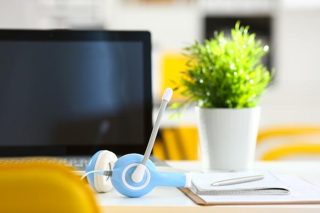 Posto di lavoro vuoto dell'ufficio remoto con il computer portatile e la cuffia avricolare