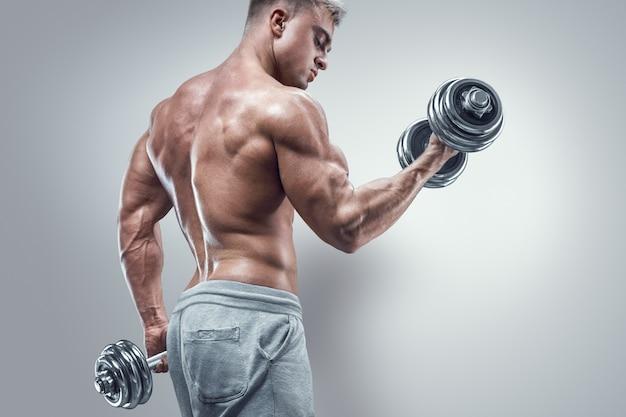 Potere l'uomo atletico in allenamento pompare i muscoli con manubri