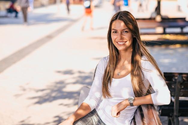 Potrait all'aperto di una ragazza casuale sorridente che si siede su una panchina, che guarda l'obbiettivo.