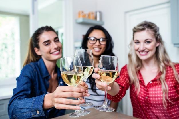 Potrait di giovani amici femminili felici che tostano bicchiere di vino