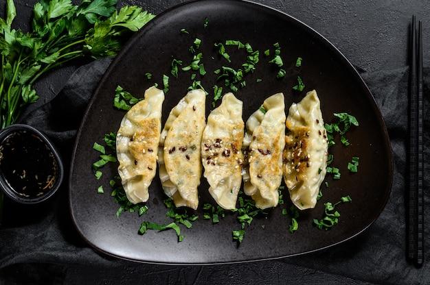Potstickers di maiale sulla tavola nera rustica