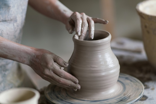 Potter scolpisce un vaso su un tornio da vasaio