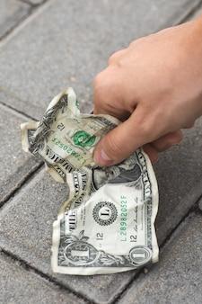 Povera donna che raccoglie una banconota in dollari vecchia e sgualcita