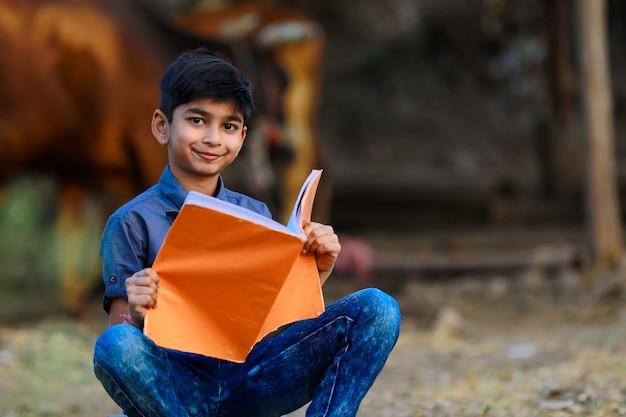 Povero bambino indiano che studia a casa