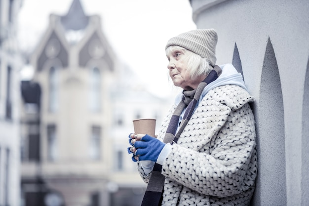Povero mendicante. triste donna anziana in piedi all'angolo di un edificio mentre elemosinava le persone per soldi