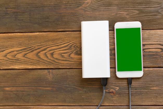 Powerbank e cellulare sulla tavola di legno
