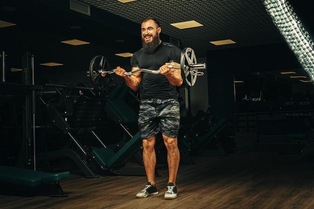 Powerlifter con forti braccia che sollevano bilanciere in una palestra