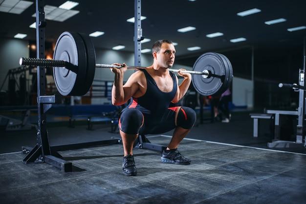 Powerlifter facendo squat con bilanciere in palestra