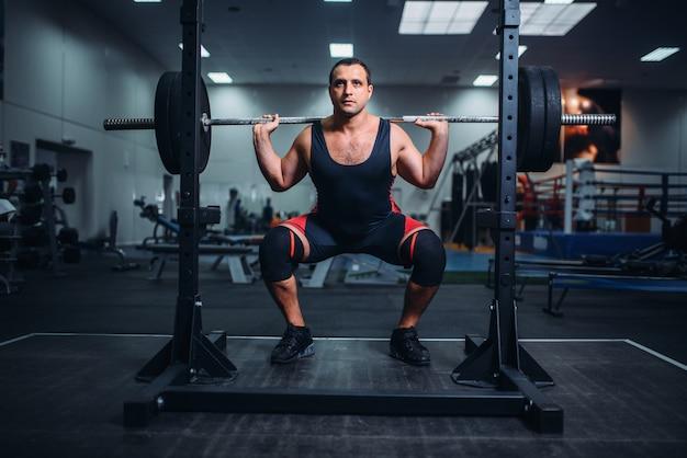 Powerlifter muscolare facendo squat con bilanciere in palestra.
