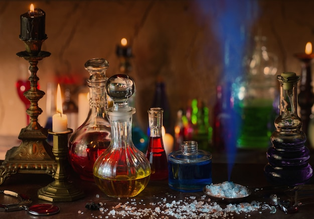 Pozione magica, libri antichi e candele su sfondo scuro