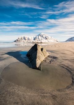 Pozza di sabbia e roccia con montagna innevata
