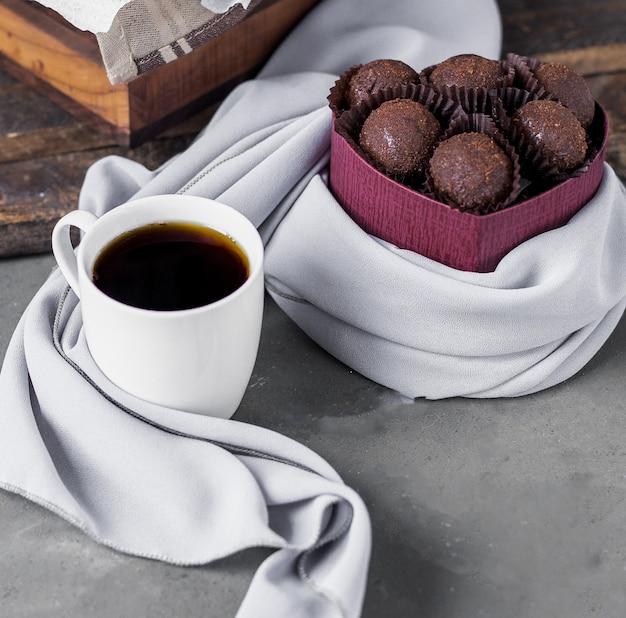 Praline al cioccolato e una tazza di caffè bianca