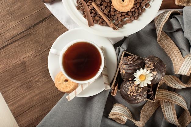 Praline e biscotti al cioccolato in un piattino con una tazza di tè