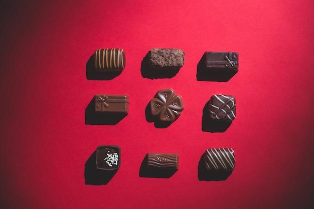 Praline isolate su ombra rossa e profonda dolce e cioccolato