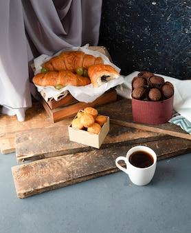 Praline, muffin, cornetti e una tazza di caffè sul tavolo blu