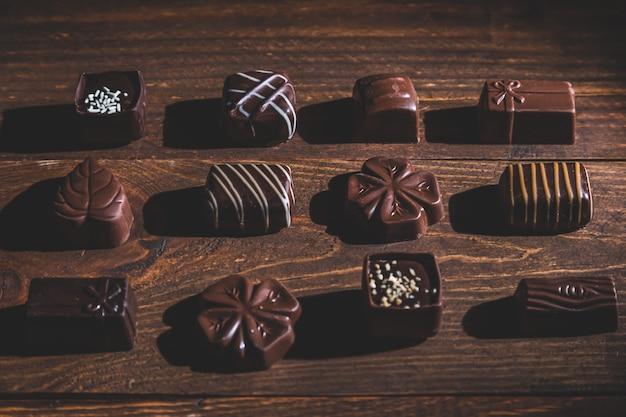 Praline su base di legno, ombre profonde, da vicino. dolce e cioccolato