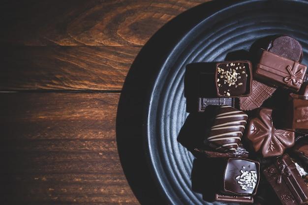 Praline sul piatto su base di legno, ombre profonde, da vicino. dolce e cioccolato.