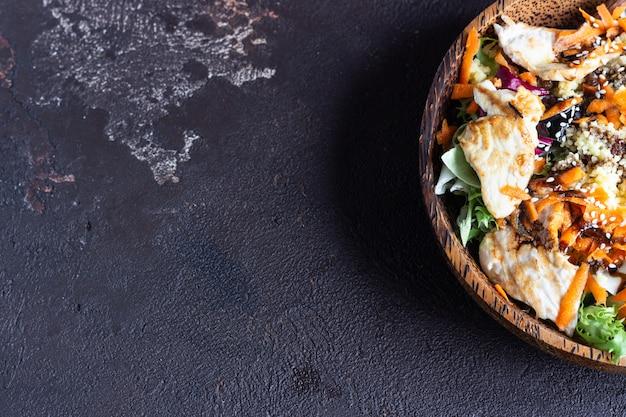 Pranzo a base di buddha con couscous, tacchino, carota, mix di insalate e sesamo.