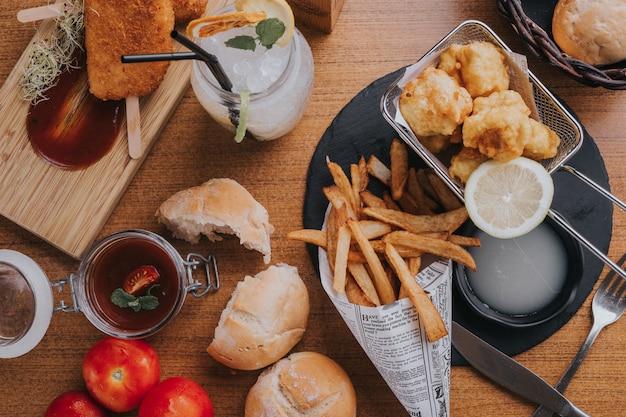Pranzo a base di pesce e patate con formaggio fritto e marmellata