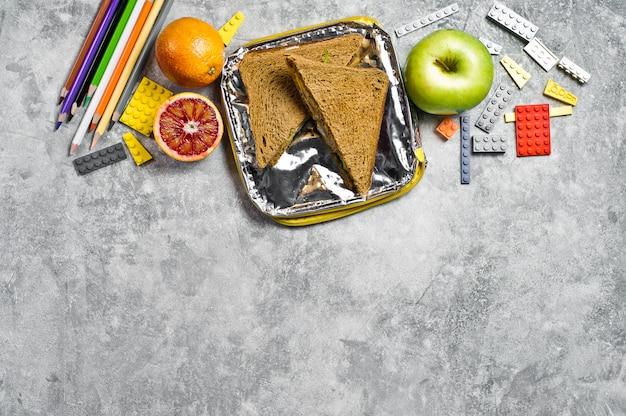 Pranzo fatto in casa per il bambino a scuola. sandwich, mela, arancia.