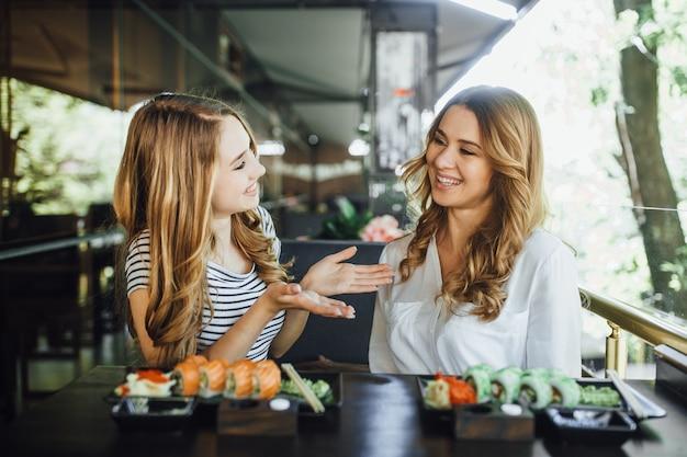 Pranzo in un ristorante cinese sulla terrazza estiva. la mamma e la sua giovane bella figlia mangiano sushi con bastoncini cinesi