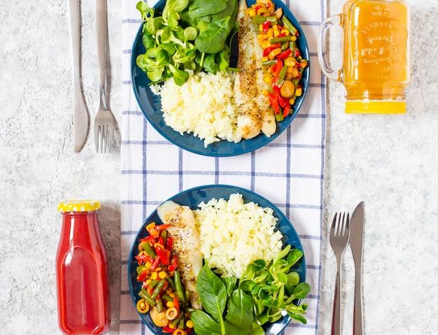 Pranzo salutare il concetto di alimentazione sana. pesce al forno, riso, spinaci freschi, lattuga, pomodorini, verdure fresche al forno