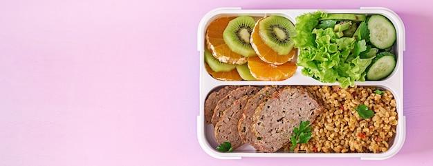 Pranzo sano con bulgur, carne e verdure fresche e frutta su un tavolo rosa. concetto di fitness e stile di vita sano. sacco per il pranzo. vista dall'alto