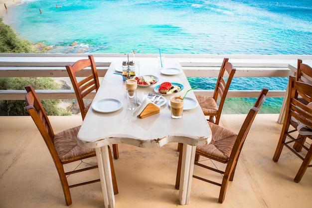 Pranzo tradizionale con deliziosa insalata greca fresca, frappe e brusketa servita a pranzo nel ristorante all'aperto con splendida vista sul mare e sul porto