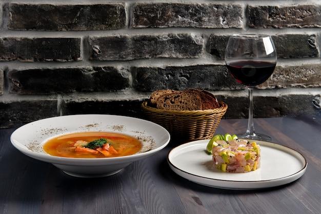 Pranzo tradizionale con zuppa di salmone e tartaro di aringhe