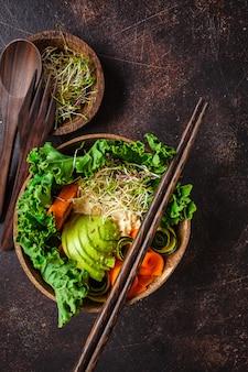 Pranzo vegano sano in ciotola di cocco. ciotola del buddha su uno sfondo scuro.
