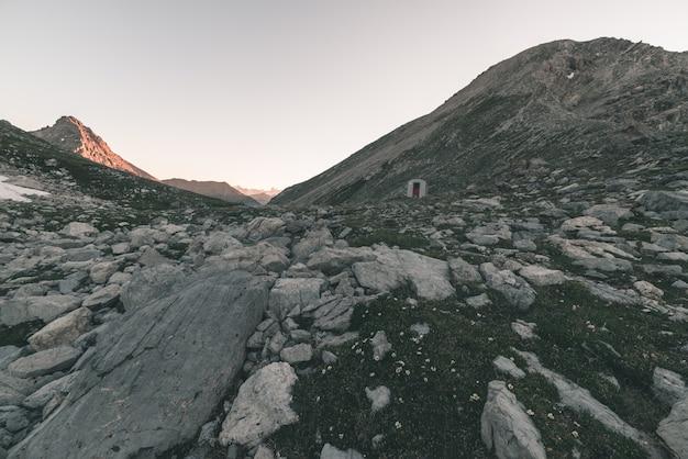 Prati e pascoli alpini incastonati in una catena montuosa d'alta quota a tramonti. le alpi italiane, famosa meta di viaggio in estate. immagine tonica, filtro vintage, tonalità divisa.