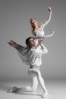 Pratica di due giovani ballerini di balletto. attraenti interpreti danzanti in bianco