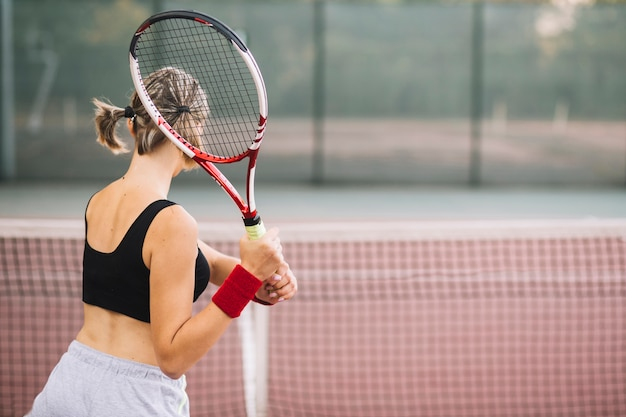 Pratica femminile del tennis di vista laterale
