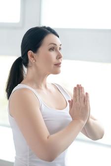 Pratica yoga. donna bruna che esegue namaste, premendo le mani insieme